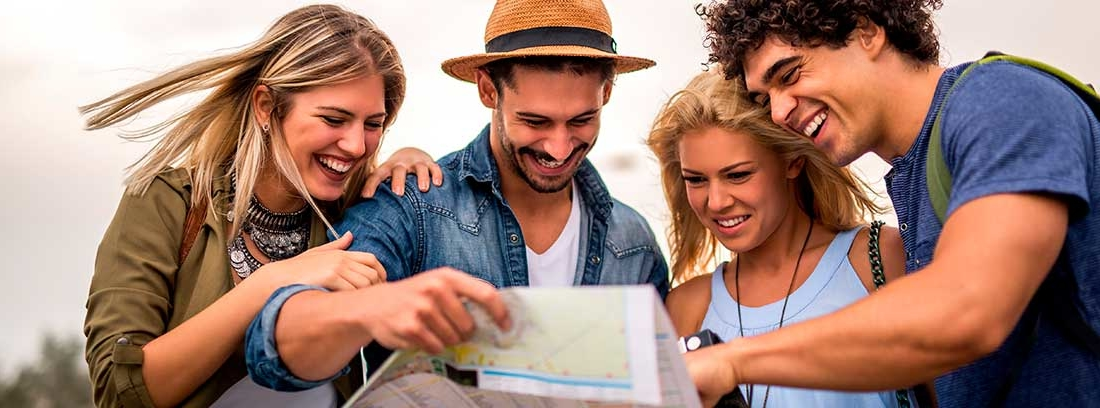 Un grupo de jóvenes turistas revisan un mapa de manera sonriente