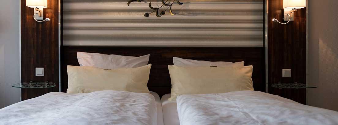 Habitación en tonos marrones con cama doble de matrimonio decorada con cojines blancos. En los laterales dos apliques encendidos