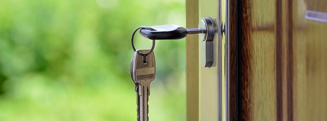 Llaves metidas en la cerradura de una puerta abierta