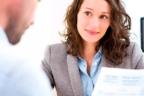 Mujer sonriente frente a un hombre con papeles en la mano