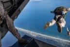 Persona con traje militar mira como otros con paracaidas flotan en el aire