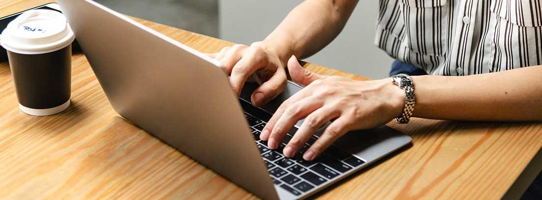 Ordenador portátil en mesa con manos con reloj sobre teclado y junto a vaso desechable