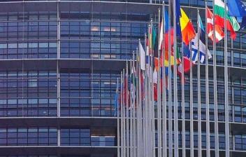 Diferentes banderas de países de Europa ondeando delante de edificio de cristales