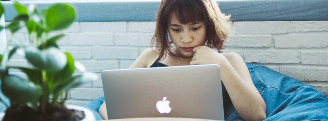Mujer recostada con ordenador portátil sobre ella y móvil sobre una mesa
