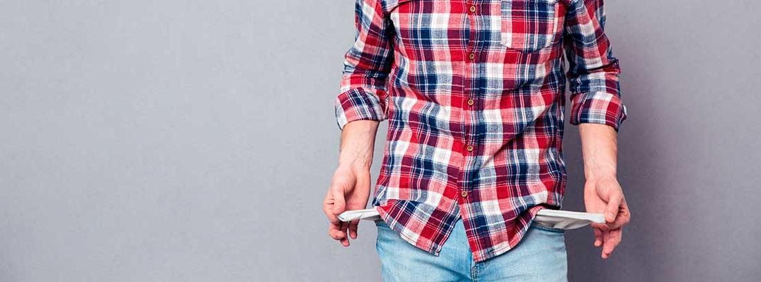 Un joven vestido con una camisa de cuadros y pantalón vaquero apoyado en una pared gris muestra sus bolsillos vacíos