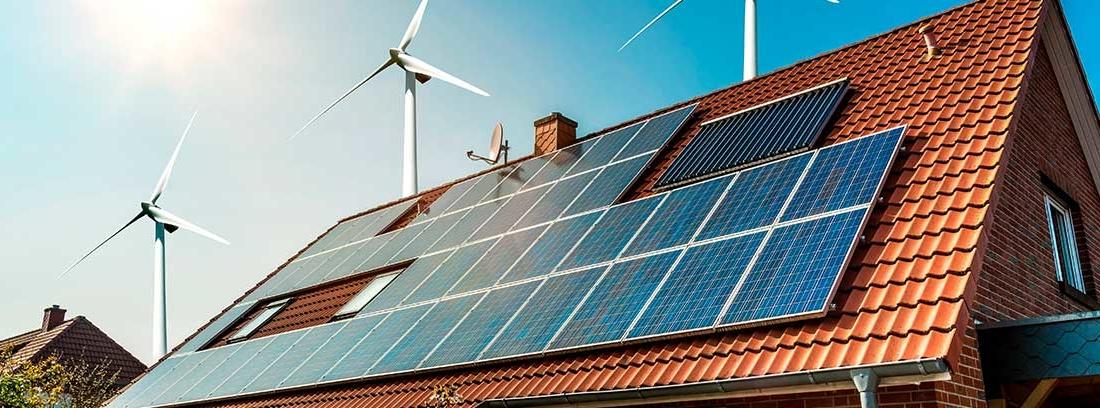 Casa con molinos de viento y paneles fotovoltaicos en el tejado