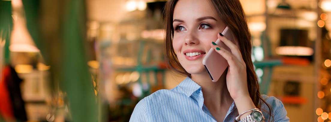 Mujer con camisa azul con móvil sobre la oreja y una taza delante de ella