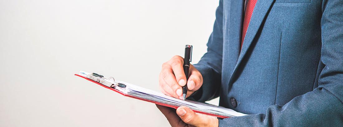 Un hombre trajeado escribe en una libreta con un bolígrafo negro
