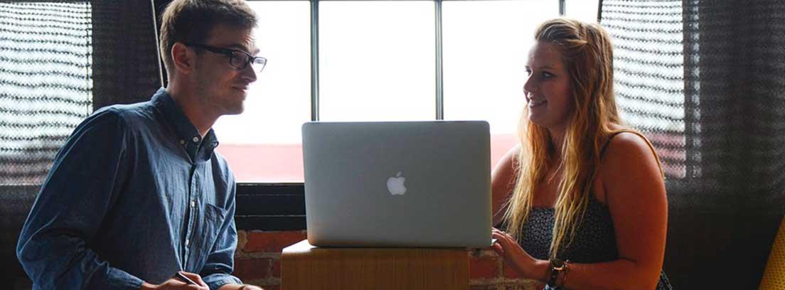 Hombre y mujer sentados una a cada lado de una mesa con ordenador portátil entre ellos