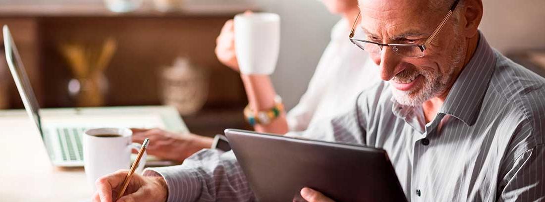 Una pareja madura sonriente se encuentra sentada en una mesa. El hombre sostiene una tablet y escribe sobre una libreta. La mujer se encuentra al fondo algo difuminada escribe en un ordenador y sostiene una taza de café