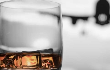 Vaso de whisky en primer plano y al fondo un avión