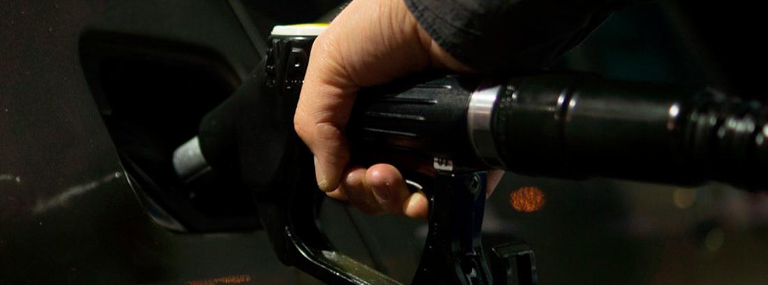 Mano sujeta manguera de surtidor de carburante dentro de depósito de coche