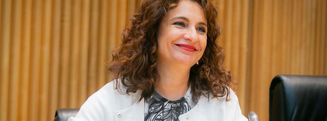 María Jesús Montero con chaqueta blanca y sonrisa sentada ante micrófono