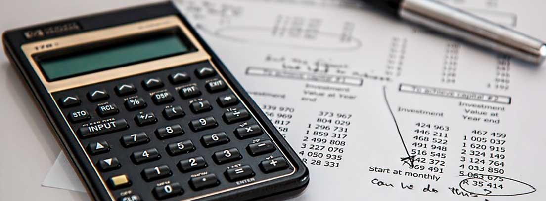 Calculadora sobre papeles con números y letras y bolígrafo al lado