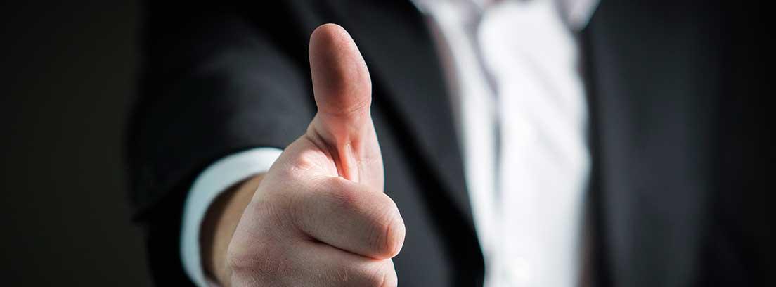 Hombre con traje extendiendo el puño con el pulgar hacia arriba