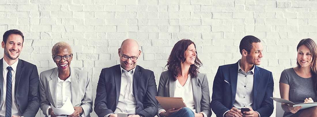Varias personas sonrientes sentadas en hilera delante de una pared de ladrillo con papeles y móviles en las manos
