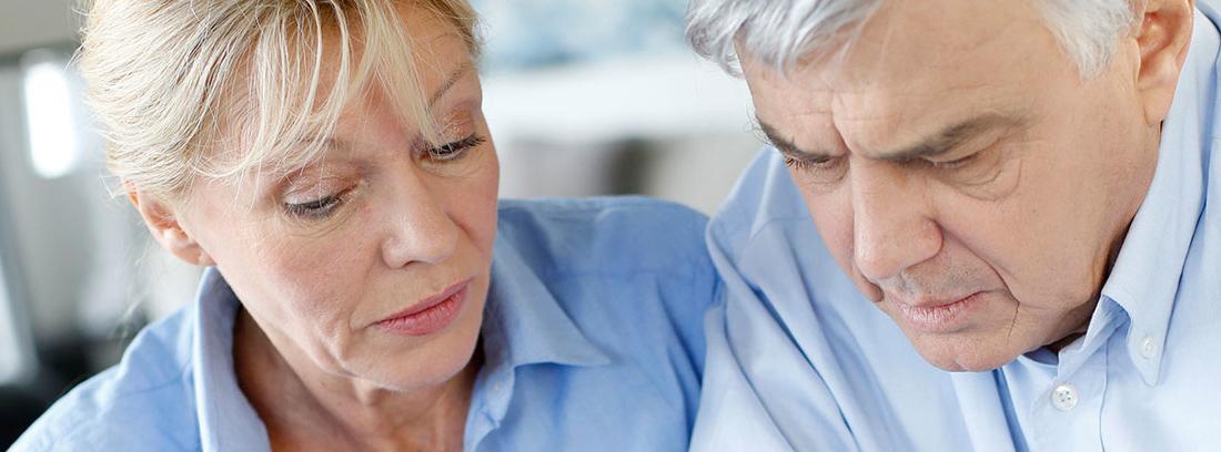 Una pareja de ancianos revisa unos datos con preocupación sobre una mesa en la que hay un ordenador