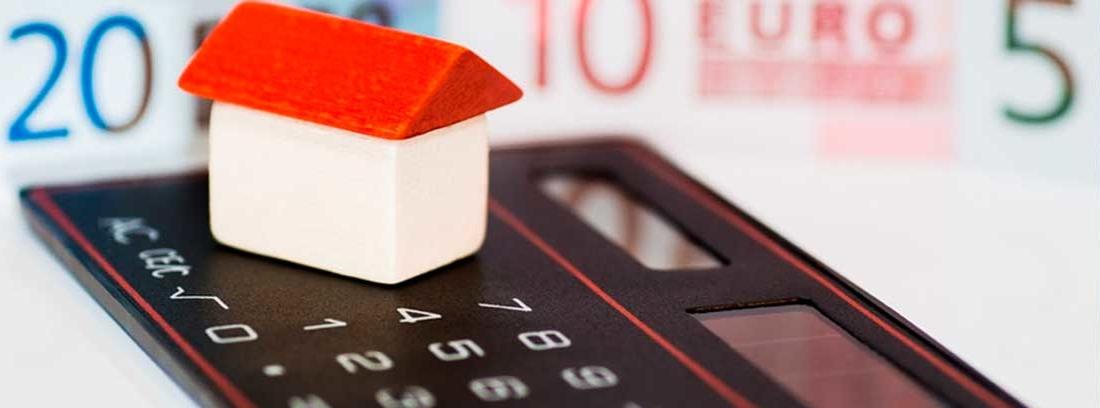 Calculadora negra y plana con una maqueta de casa blanca con tejado rojo