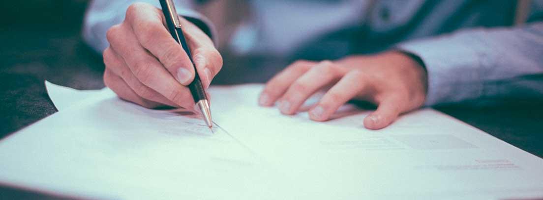 Manos con boli escribiendo en unos papeles