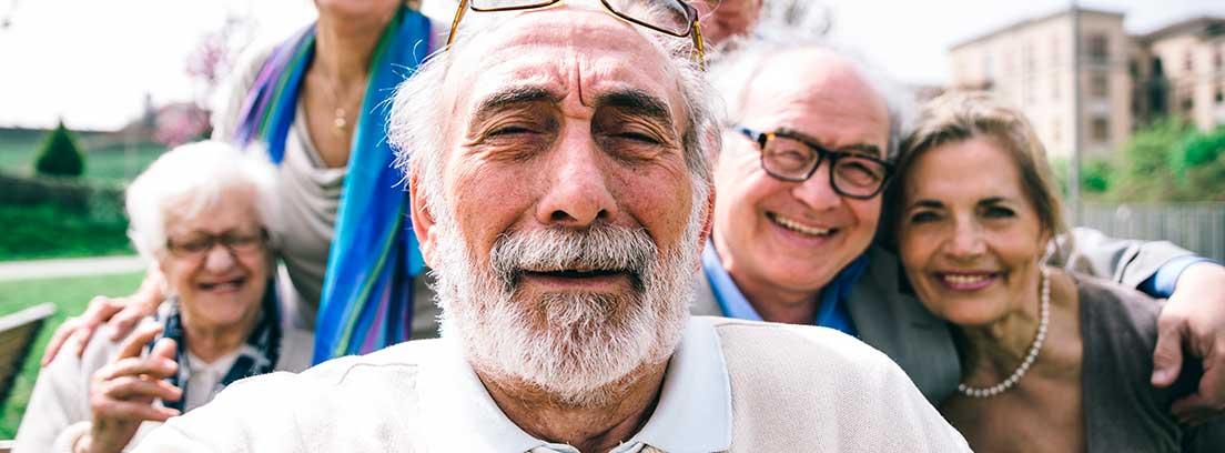 Un grupo de mujeres y hombres mayores se hacen un selfie. Todos posan sonrientes para la cámara