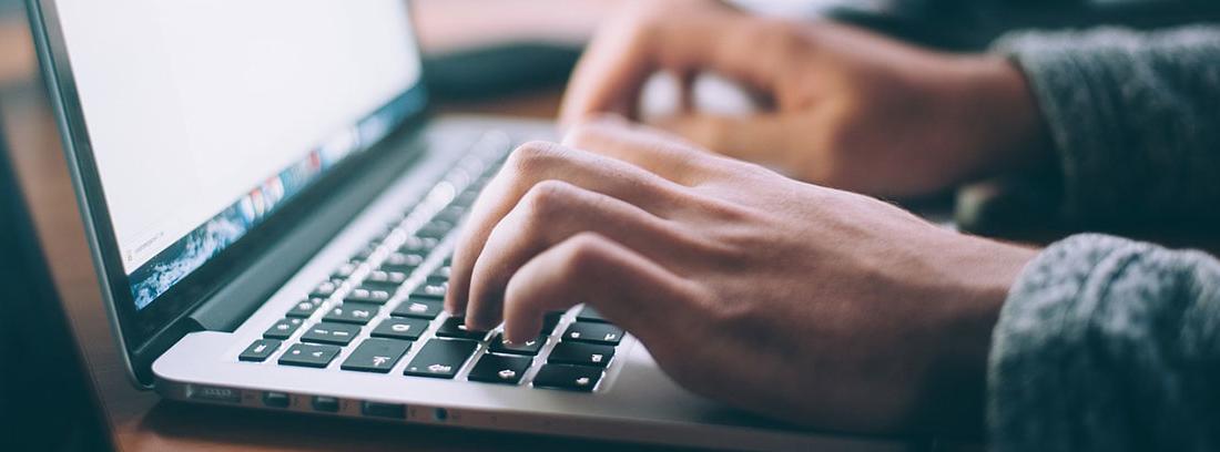 Ordenador portátil abierto con manos sobre su teclado
