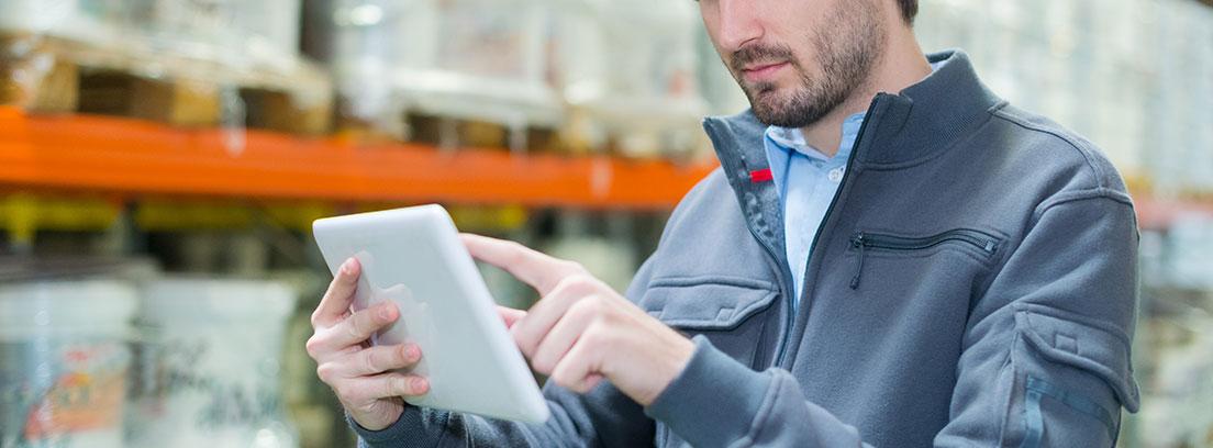 Hombre con tableta blanca en la mano apunta sobre la pantalla con un dedo