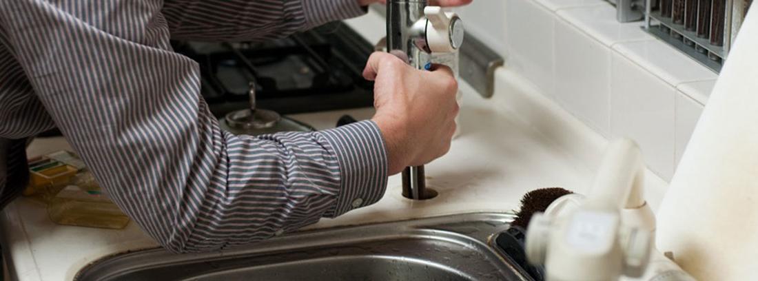 Un hombre repara el grifo de una cocina