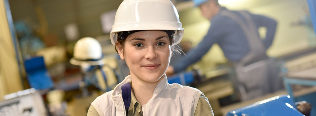 Trabajadora de una fábrica vestida con un mono de trabajo y un casco blanco. Al fondo más personas trabajando y máquinas de color azul