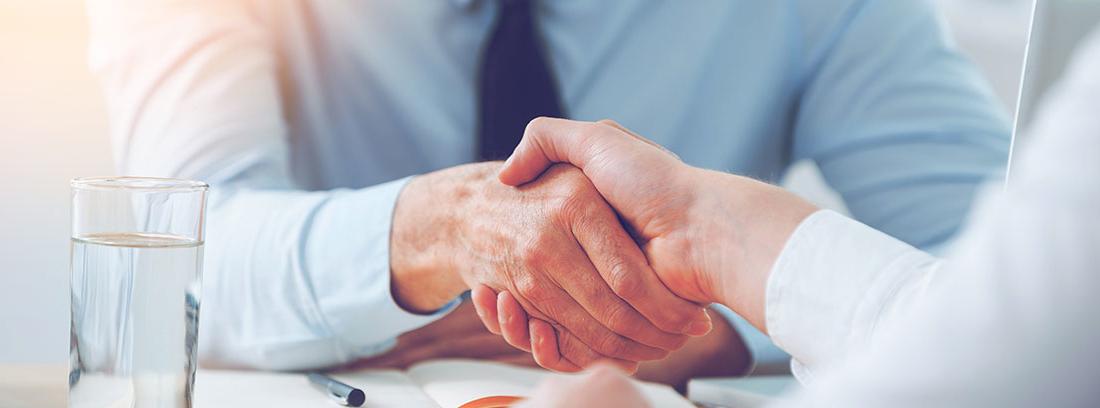 Un hombre sonriente vestido con camisa y corbata azul estrecha la mano a una mujer vestida de blanco
