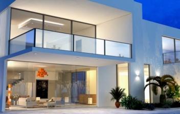 Casa cuadrada y blanca con grandes cristaleras y junto a piscina de noche