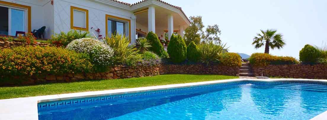 Piscina exterior con agua y fondo azul al lado de casa y jardines