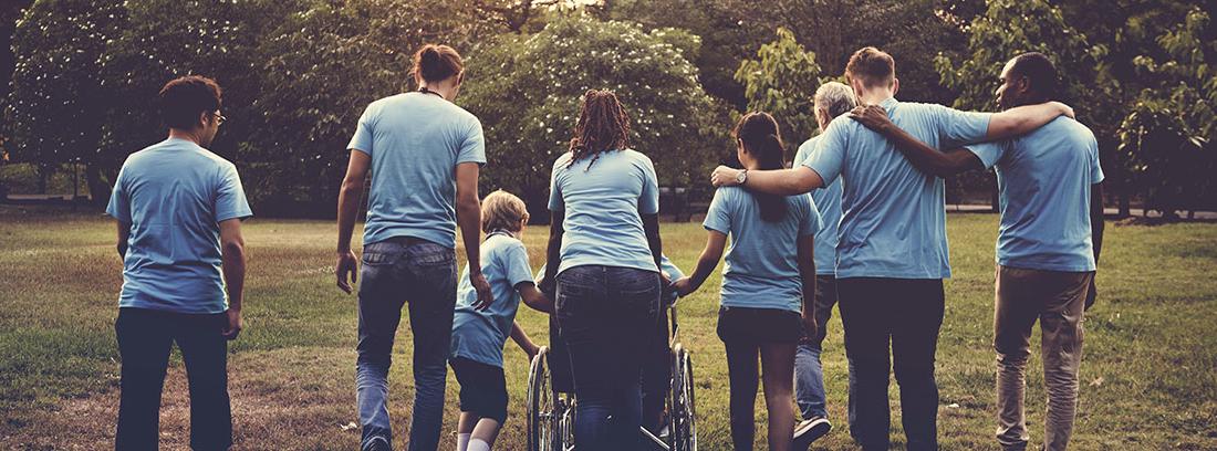 Grupo de voluntarios de distintas edades con camisetas azules pasean a una persona en silla de ruedas