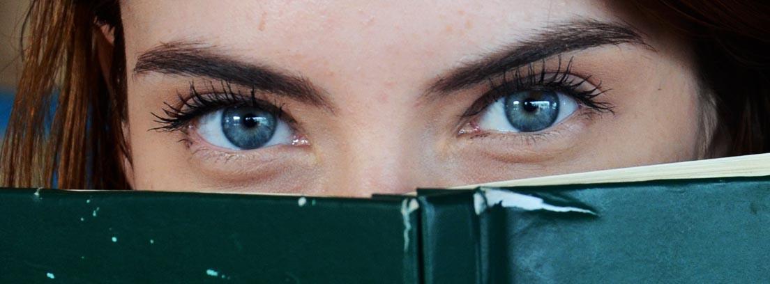 Mujer asomándose por encima de un libro abierto
