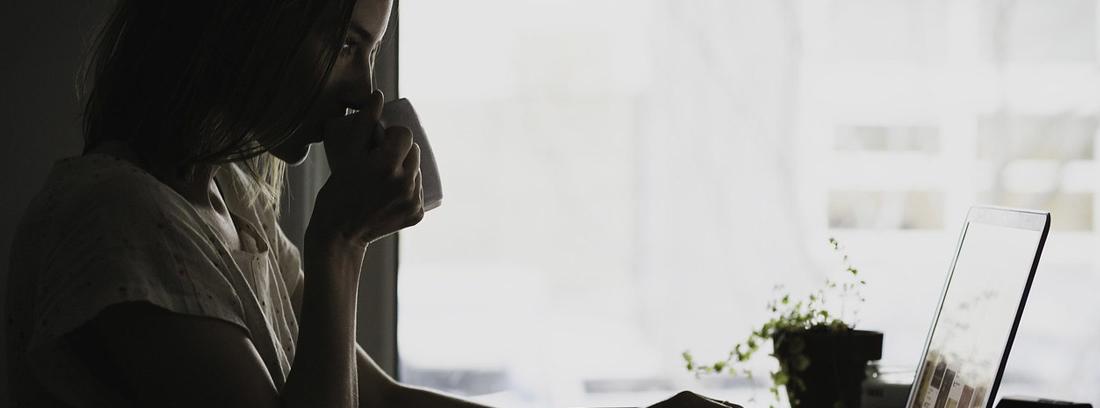 Mujer con taza en la mano y sobre sus labios sentada delante de ordenador portátil