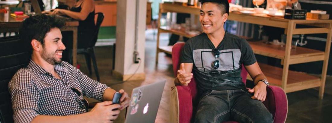 Hombre con camisa de cuadros y portátil sobre las rodillas junto a otro hombre