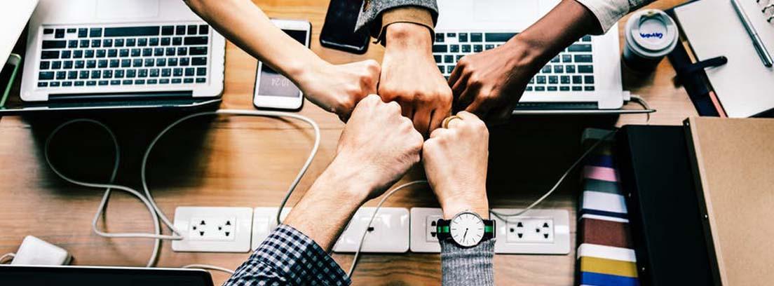 Diferentes brazos en círculo unen sus puños en el centro sobre una mesa con ordenadores