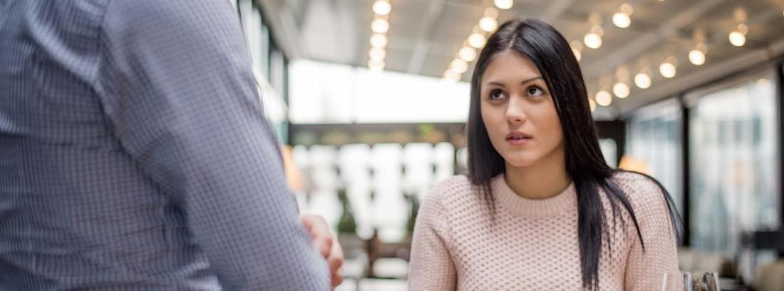 Mujer en un restaurante señalando su comida a un hombre de pie y de espaldas