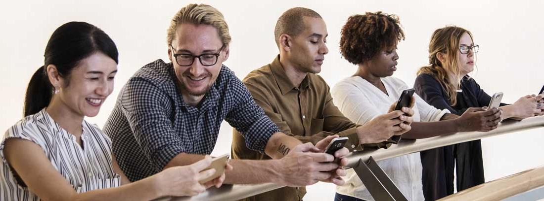 Diferentes personas apoyados sobre barandilla con teléfonos móviles en las manos