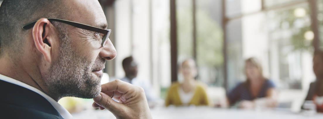 Hombre con barba canosa y gafas se toca la barbilla en una mesa con más personas