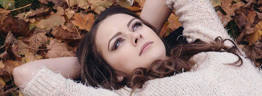 Mujer con las manos tras la cabeza tumbada sobre hojas secas y marrones