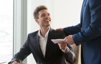 Un hombre de pie y con traje da un sobre a un trabajador feliz sentado en una mesa