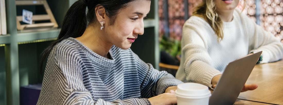 Mujer con sentada y con manos sobre teclado de portátil junto a otra mujer que mira