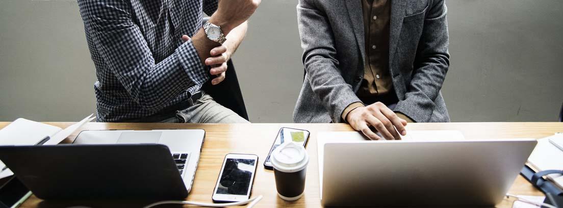 Dos hombres sentado delante de una mesa con ordenadores portátiles y móviles