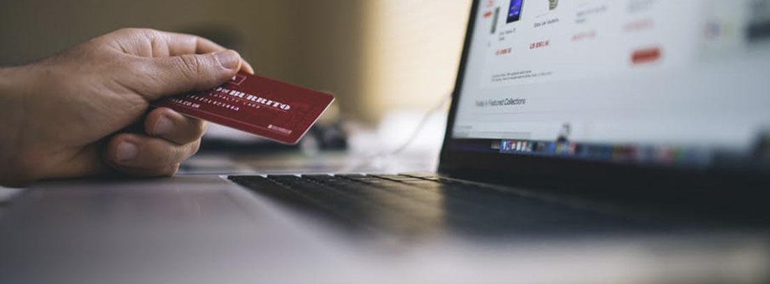 Mano sujeta tarjeta roja delante de pantalla de ordenador y sobre el teclado