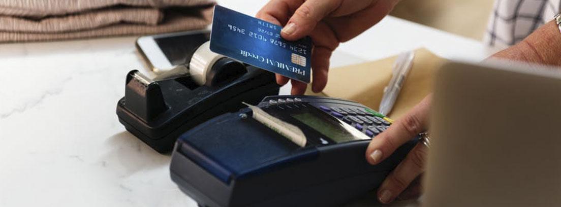 Mano sujeta una tarjeta de pago azul junto a una terminal de pago negra