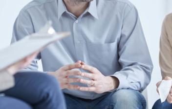Dos personas sentadas frente a una tercera con papeles en la mano