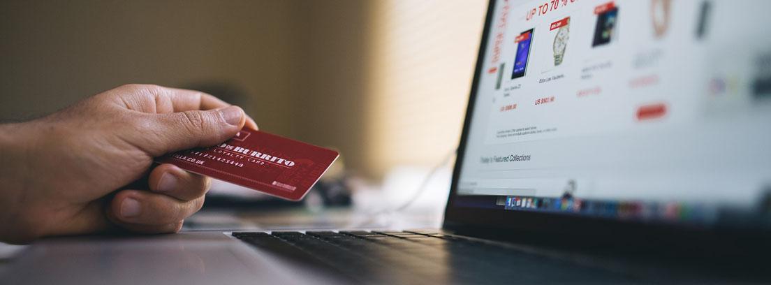 Mano sujetando una tarjeta de crédito sobre un ordenador