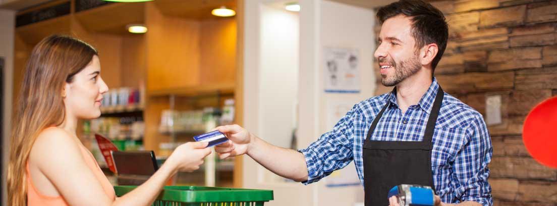 Hombre con delantal dando una tarjeta a una mujer
