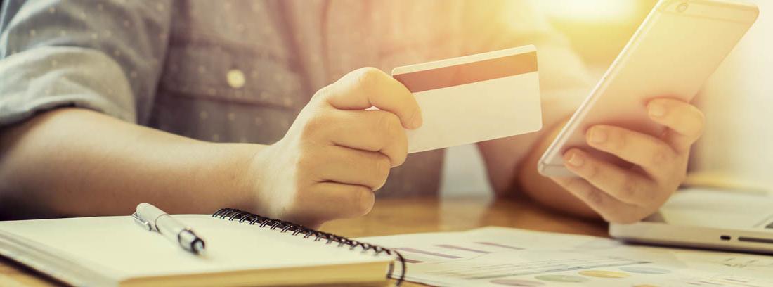 Persona con tarjeta bancaria en una mano y un móvil en la otra, sentada frente a una mesa con cuadernos y papeles