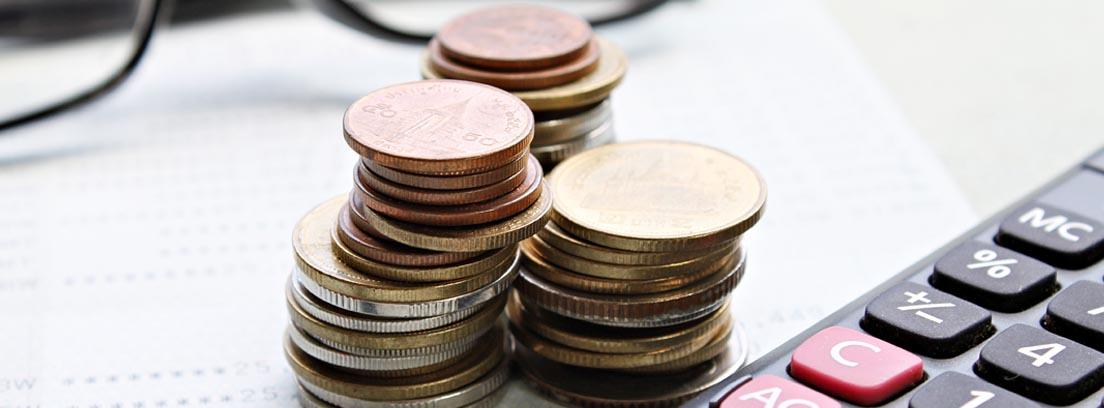 3 montones de monedas al lado de boli, gafas y calculadora